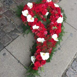 Stort blomster hjerte med hul i midten i røde og hvide blomster.