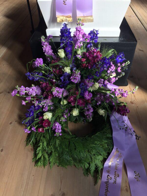 Smuk krans i blå og lilla blomster dekoration på krans af årstidens grønt med bånd