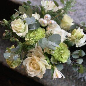 Blomsterbuket tæt bundet i hvide og lime farver med jule kugler