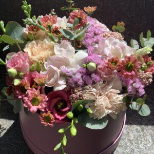 Blomster i hatteæske i lyserøde farver lavet i Oasis og kan vandes i æsken