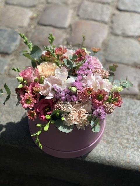 Blomster i hatteæske Afskåret friske blomster pyntet i Oasis i en hatteæske lavet efter sassonen